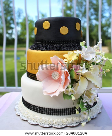 Three tier gold, black, and white wedding cake outdoors