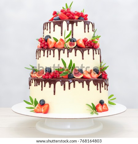 Three-tiered wedding cake in chocolate, decorated with slices strawberries, blueberries, figs, red currants and green leaves on a white background. Picture for a menu or a confectionery catalog.