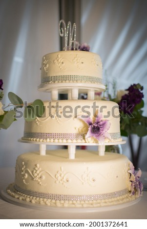Three-Tiered Wedding Cake with Purple Flowers and an M on Top Photo stock ©