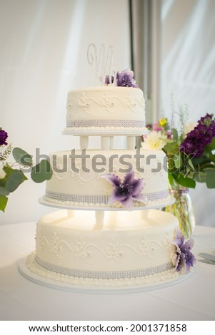 Three Tiered Wedding Cake with Purple Flowers and M on Top Photo stock ©