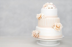 Three-tiered white wedding cake decorated with flowers from mastic on a white wooden table. Picture for a menu or a confectionery catalog with copy space.