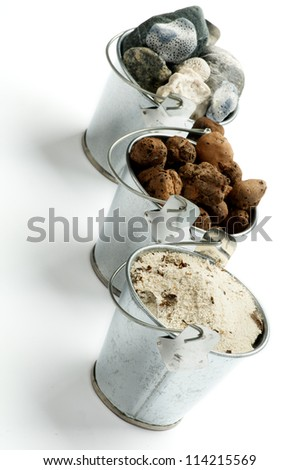 Three Tin Buckets with Gravel, Sand and Stones in a Row isolated on white background