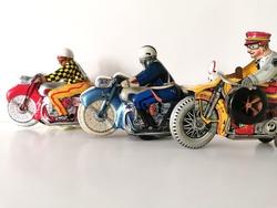 Three Tin Motorcycle Clockwork Toys on white