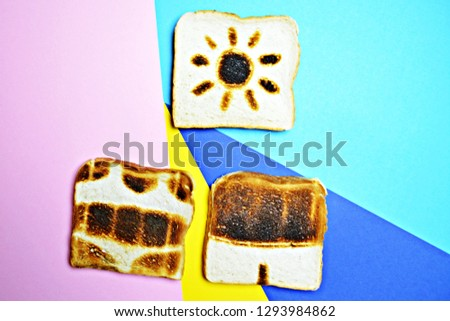 Three toasts lie on a colorful background - these are not toasted on the whole surface but show the contours of trunks and bikini and those of a sun - concept of sunburn presented with toasts #1293984862