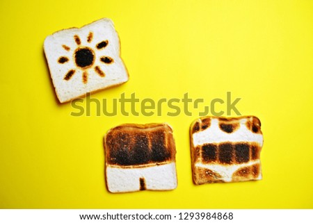 Three toasts lie on a colorful background - these are not toasted on the whole surface but show the contours of trunks and bikini and those of a sun - concept of sunburn presented with toasts #1293984868
