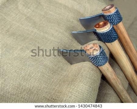 Three tomahawks, also known as hawks, displayed on burlap with bokeh effect. Made from rasps. These will be used at throwing competitions. #1430474843