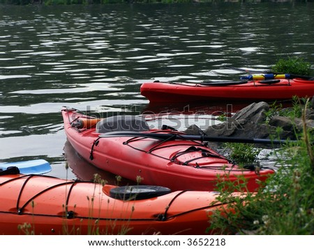 Three touring kayaks beached on the edge of the Potomac River. - stock photo