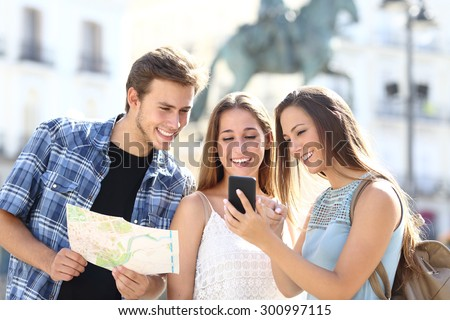 Three tourist friends consulting gps on smart phone in a touristic place with a monument in the background #300997115