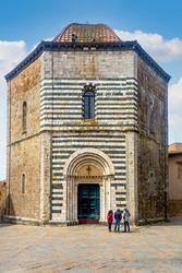 Three tourists admire Battistero di San Giovanni (Saint John Baptistry) in front of city cathedral in Volterra, Pisa, Tuscany - Italy