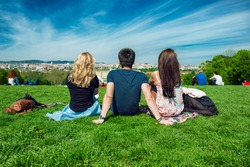 Three tourists friend sitting on the green grass with beautiful view to Vienna panorama