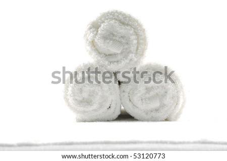 Three towel rolls on white towel