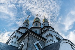 three towers of the Orthodox Christian Church of St. Eugene with cupola domes and crosses in the village. Buky, Ukraine