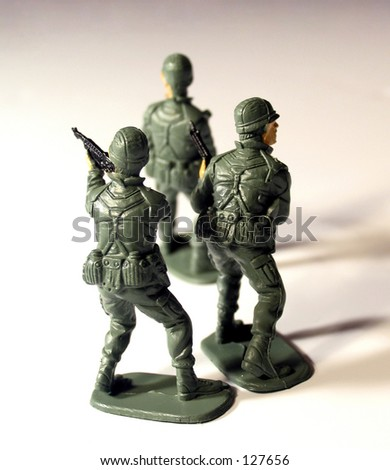 Three toy soldiers  facing backwards on white background