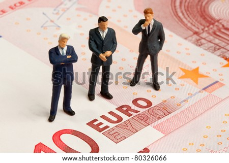 Three toy train figures on a ten euro note