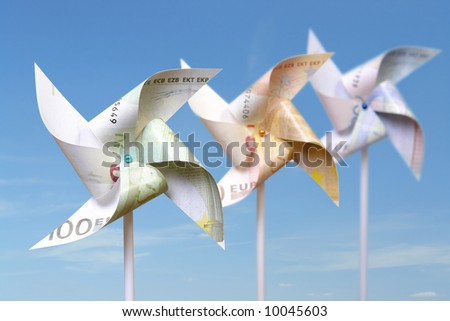 Three toy windmills cut from 100, 50 and 20 euro banknotes over blue sky