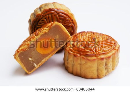 Three Traditional Mooncakes with one cut up half to show egg yolk