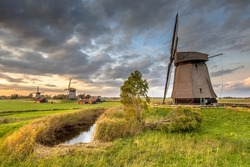 Three Traditional wooden windmills in old agricultural landscape near Schermerhorn, North Holland. Netherlands