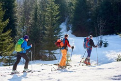 Three travelers, male skier tourists with backpacks hiking on skis in deep snow uphill through mountain forest on sunny cold winter day. Tourism, exploration and active lifestyle concept.
