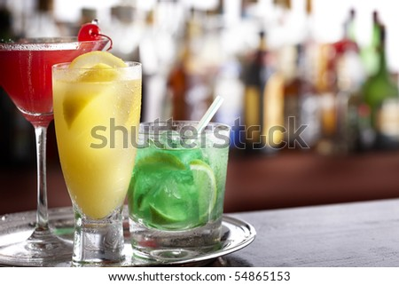 Three tropical mixed drinks sitting on silver tray, shot in bar with space for copy