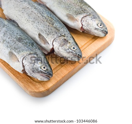 Three trout fish on wooden board, isolated on the white background - stock photo