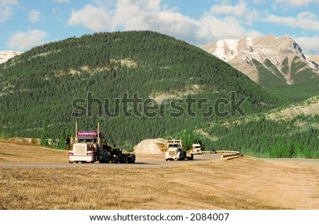 three trucks coming up the Canadian Rockies