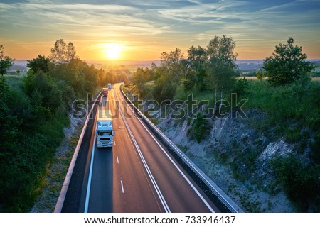 Three trucks driving on the highway in a rural landscape at sunset. View from above. #733946437