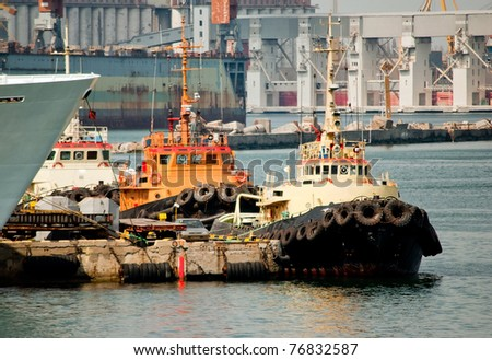 Three tug boats in the port against the industrial view