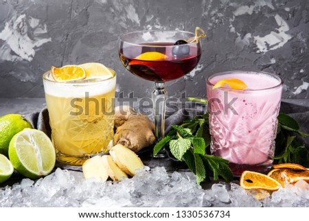 three types of alcoholic cocktails in a beautiful composition on a gray concrete background #1330536734