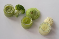 Three types of baby vegetable puree in glass jars. Broccoli puree, squash puree and cauliflower puree for the introduction of the first complementary foods for babies.