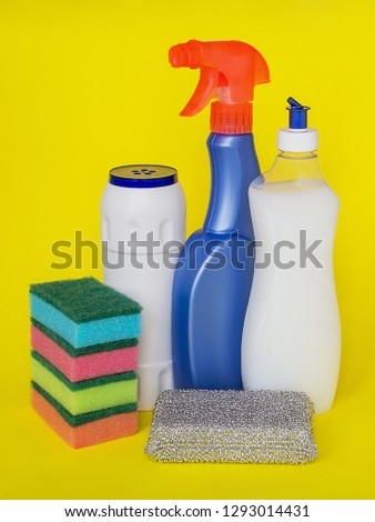 Three types of detergents for the kitchen: liquid, spray and powder and colorful foam sponge for washing dishes on a yellow background. Kitchen detergent. Household chemicals. Household chores.  #1293014431