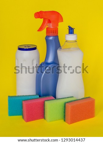 Three types of detergents for the kitchen: liquid, spray and powder and colorful foam sponge for washing dishes on a yellow background. Kitchen detergent. Household chemicals. Household chores.  #1293014437