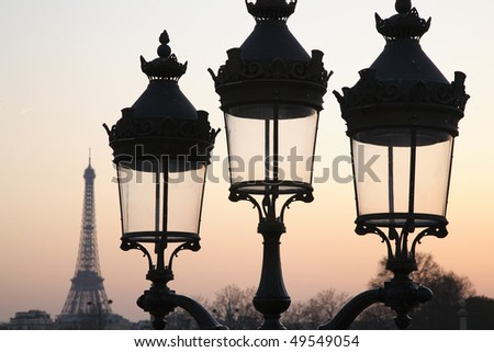 Three unlit street lamps at dusk, with the Eiffel Tower in the background. Horizontal shot.
