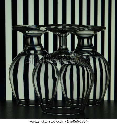 three upturned glasses on a creative background of vertical black and white stripes