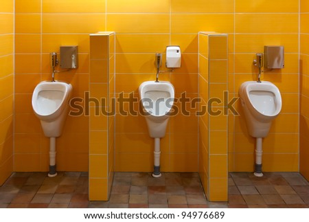 Three urinal in the bathroom with yellow walls