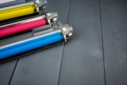 Three used toner cartridges in a color laser printer on gray wooden background for recycling