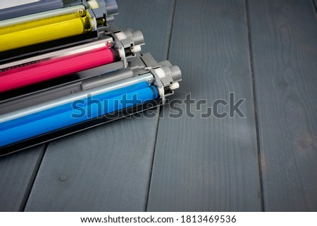 Three used toner cartridges in a color laser printer on gray wooden background for recycling Foto stock ©