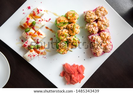 Three varieties of rolls with different fillings of seafood and wasabi on a square plate in the restaurant. Flatlay