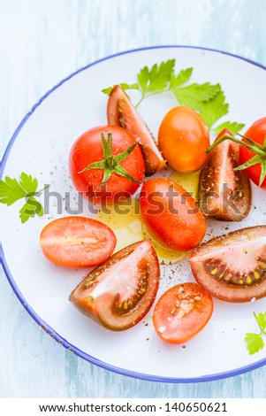 Three varieties of whole and halved tomato on a plate including grape tomatoes, cherry tomatoes and a purple-red variety