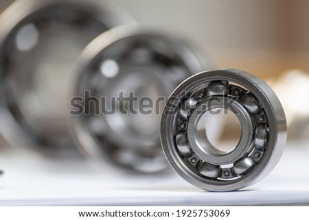 Three various ball bearings lying on table. Automotive spare part sale company. Heavy industry engineering company. Machinery designing and manufacturing. Steel details for engine mechanisms. Сток-фото ©