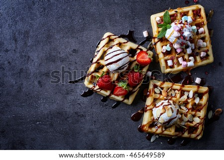 Three various belgian waffles on dark wooden background. From top view