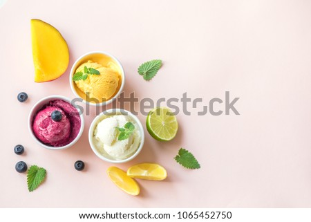 Three various fruit and berries ice creams on pink background, copy space. Frozen yogurt or ice cream with lemon, mango, blueberries - healthy summer dessert.
