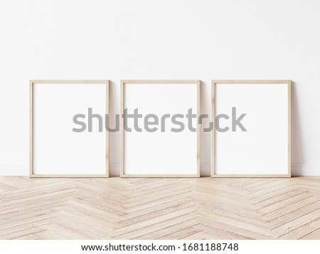 Three vertical wooden frame poster on wooden floor with white wall. 3 frame mock up. 3D illustration.