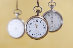 Three vintage pocket watches with golden background