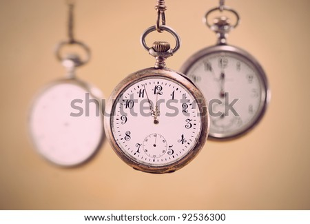 Three vintage pocket watches with golden background