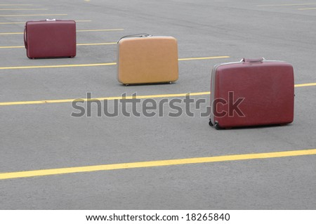 Three vintage suitcases on a parking lot