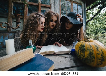 Three vintage witches perform magic ritual, at the table, reading a magical book on the eve of Halloween #652284883