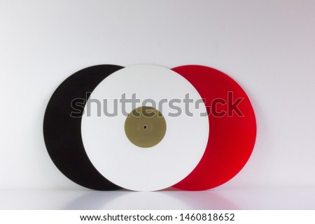 Three vinyls, black, red and white, on white background, with white space.