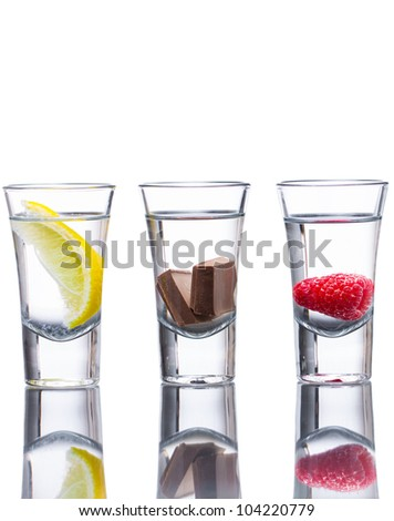 Three vodka shots flavored with raspberry, lemon, and chocolate. Reflection in table and isolated on white.