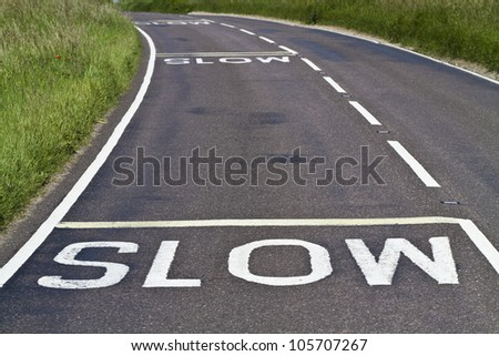 Three warning signs to slow down painted on a curving road - stock photo
