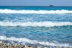 three waves near the shore. a blurred ship on the horizon. Sea waves, water tide. High quality photo
